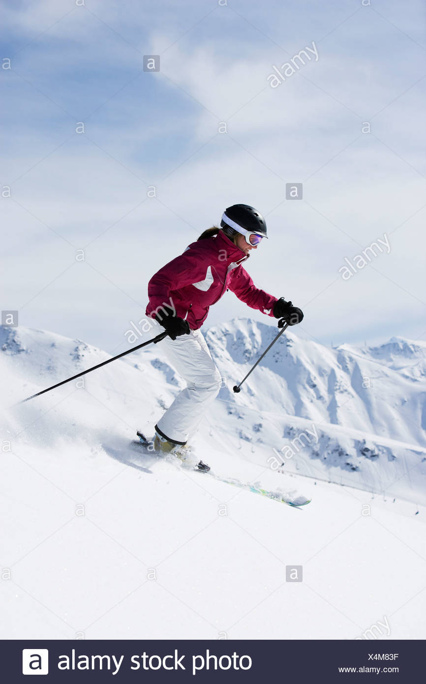 Woman in red & white outfit off-piste. - Stock Image
