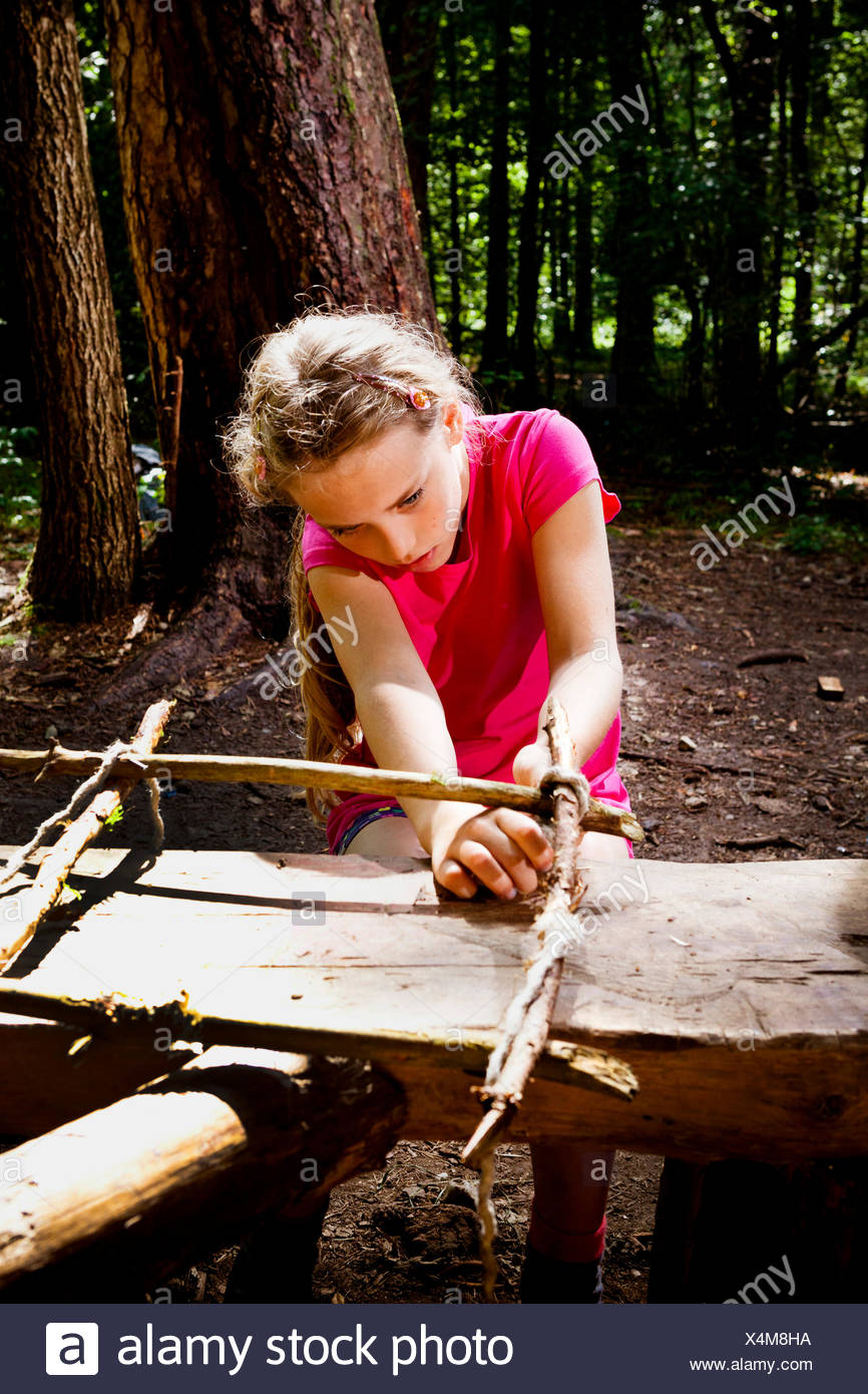 Girl crafting in a forest camp, Munich, Bavaria, Germany - Stock Image
