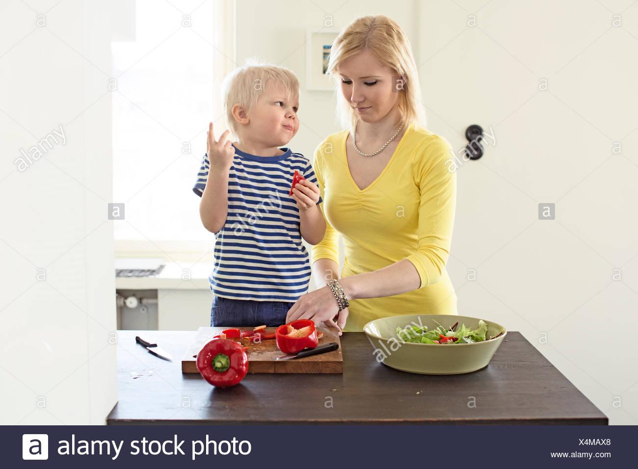 Finland, Helsinki, Kallio, Mother and son making salad in kitchen - Stock Image