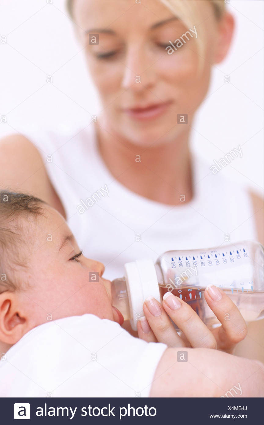 Mother bottle-feeding baby. Mother using a bottle to feed milk to her 2-month-old baby boy. - Stock Image