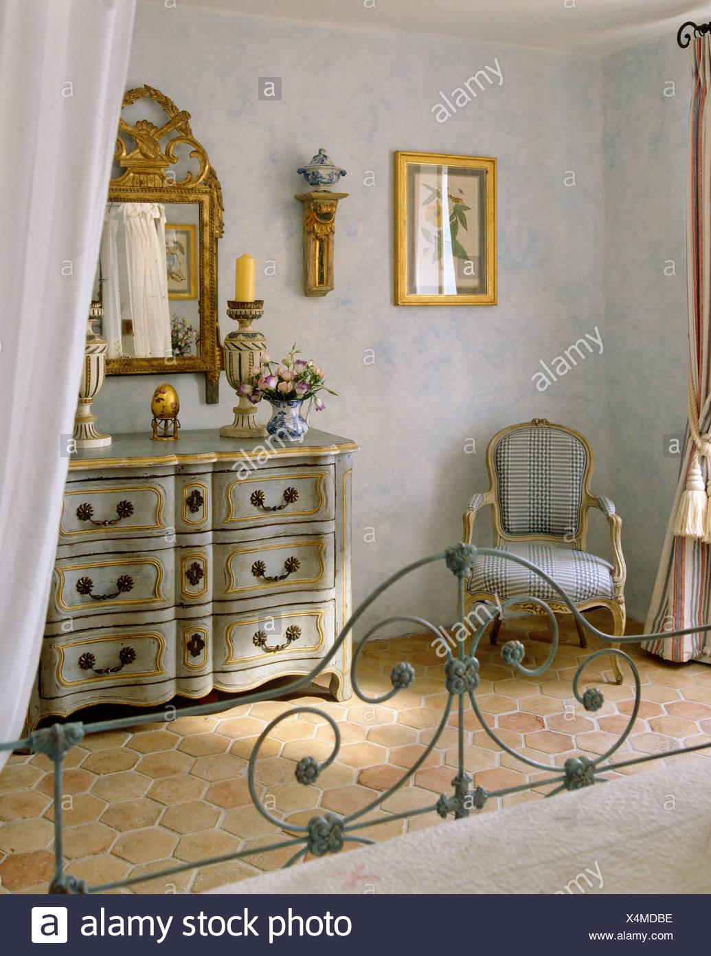Wrought-iron bed in pale gray French country bedroom with ...