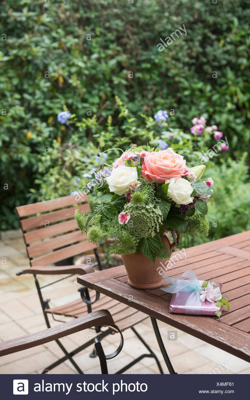 Gift with bouquet of flowers on table in garden, Munich ...