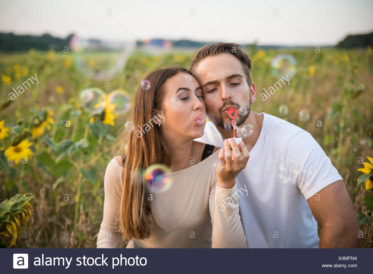Couple blowing bubbles in field - Stock Image