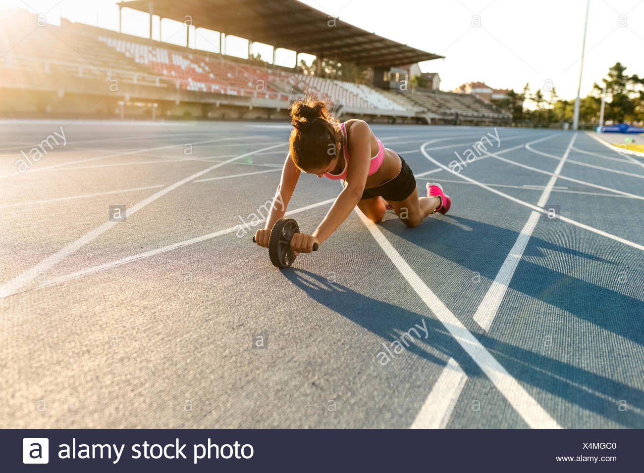 Female athlete doing strength training with a roller - Stock Image