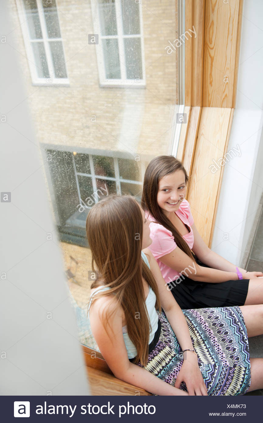 Sweden, Teenage girls (14-15) talking on window sill - Stock Image