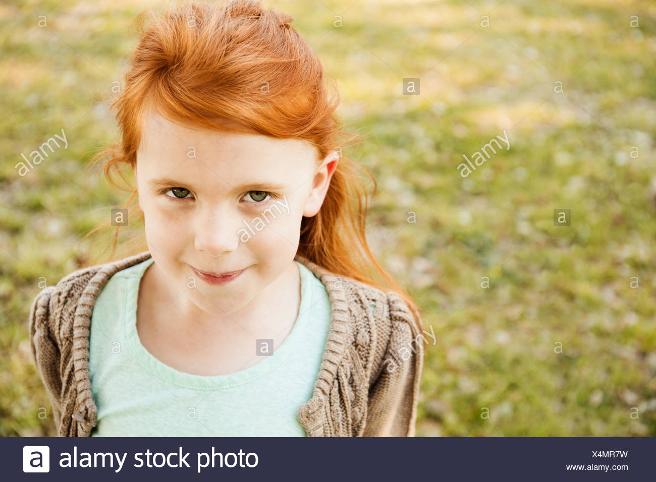 Portrait of red haired girl in park - Stock Image