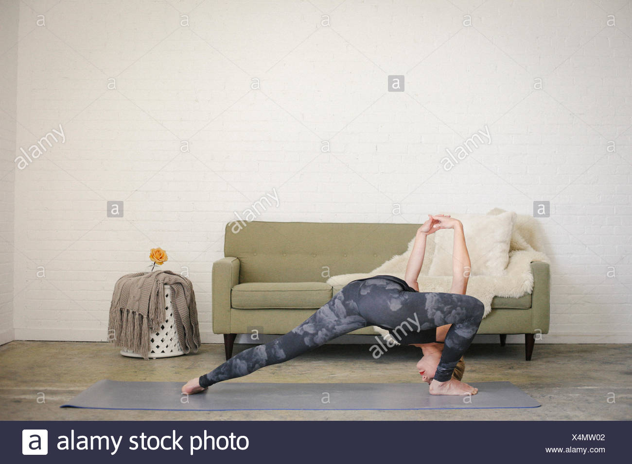 A blonde woman in a black leotard and leggings, standing on a yoga mat in a room, doing yoga, her legs apart and arms raised. - Stock Image