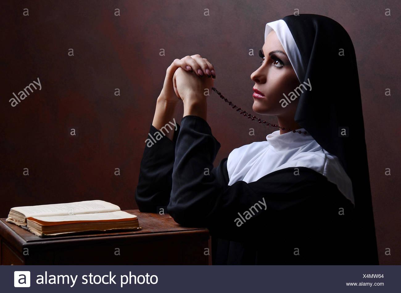 Young attractive nun praying - Stock Image
