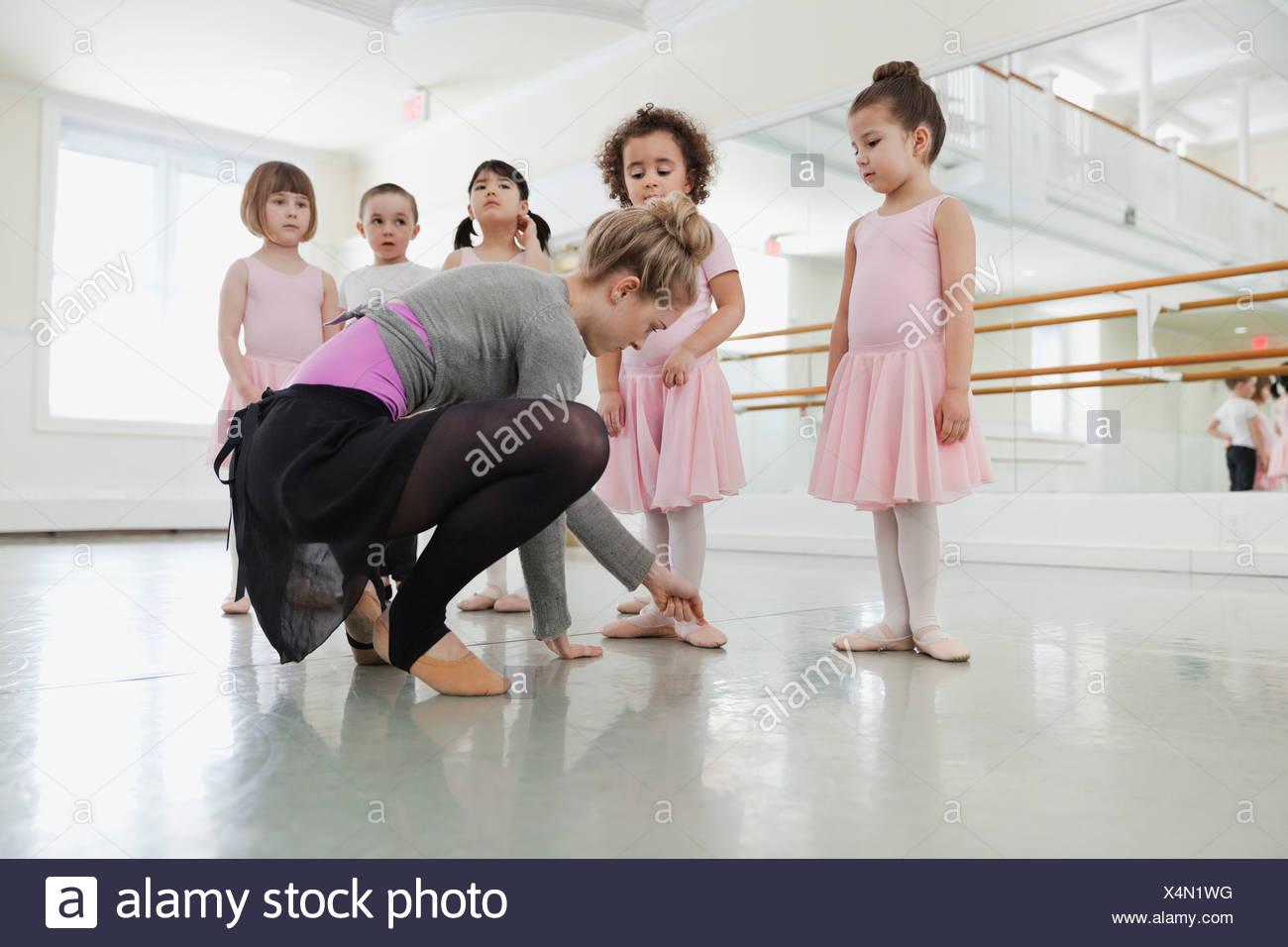 Female ballet instructor teaching children in ballet studio - Stock Image