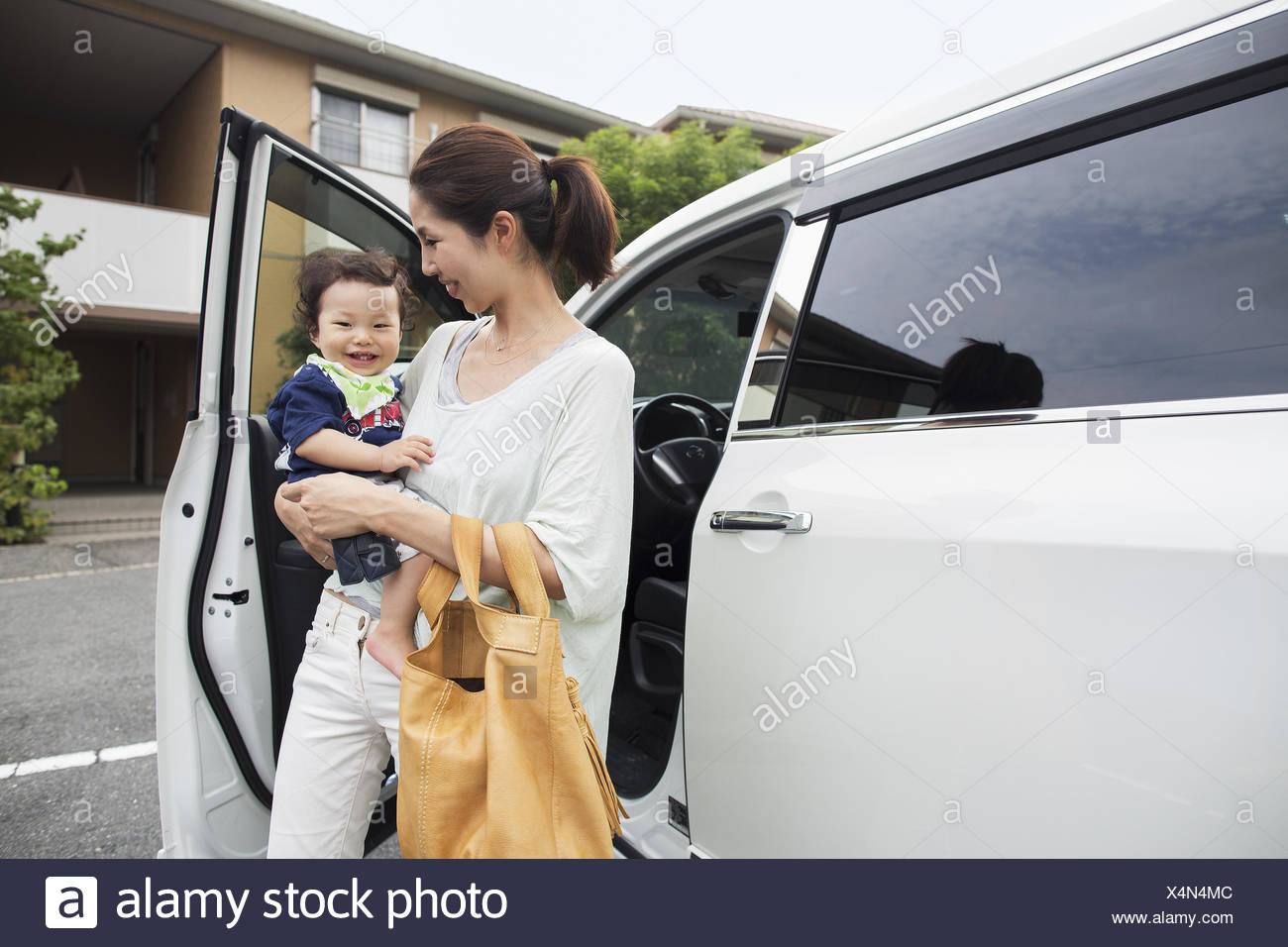 Mother carrying her baby boy by their car. - Stock Image