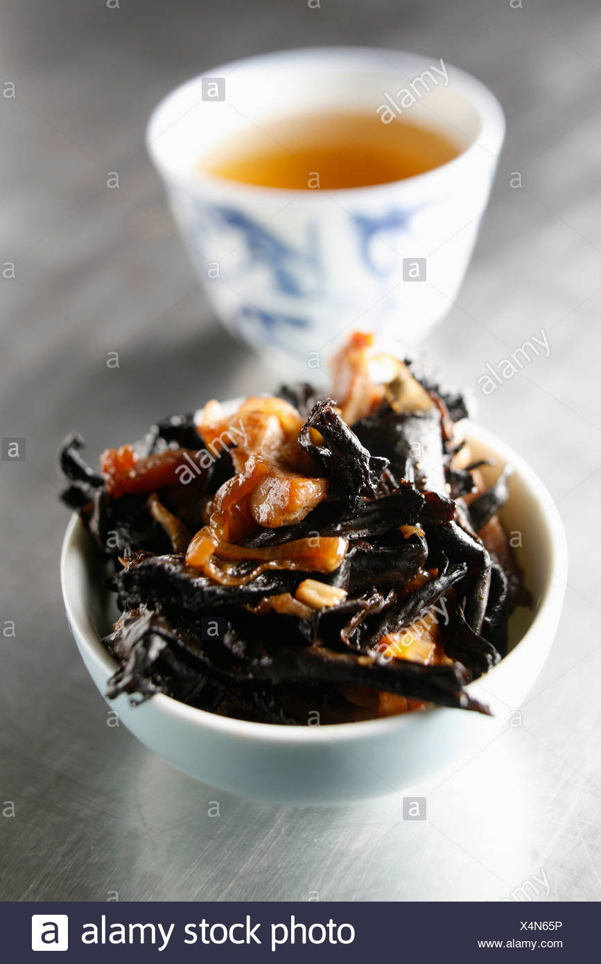 Thinly sliced veal with black trumpette mushrooms - Stock Image