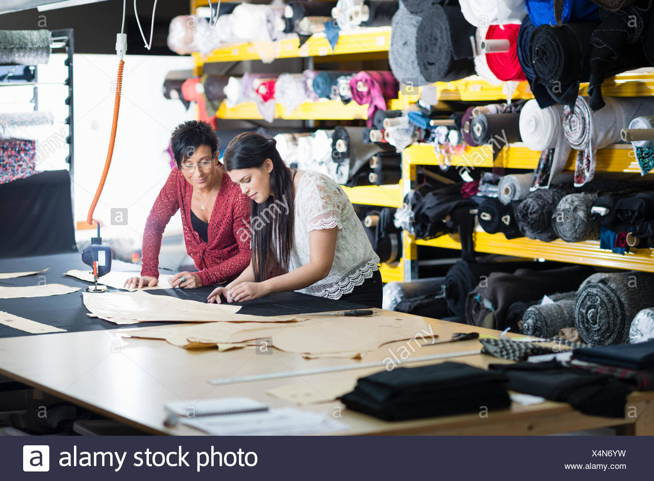 Two seamstresses chalking design onto textile on work table - Stock Image