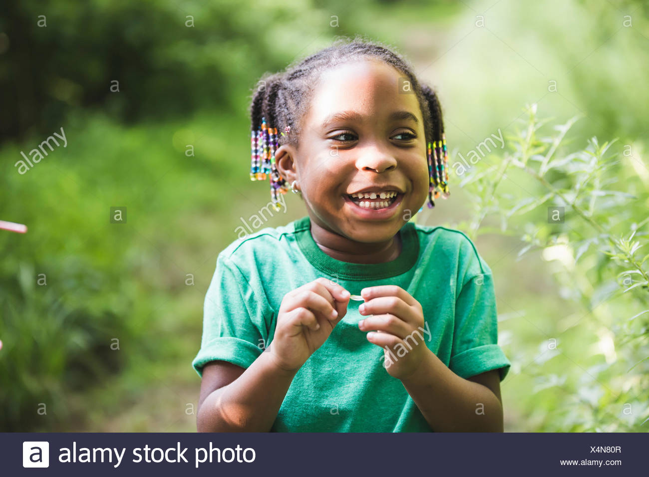 Portrait of girl with plant in parkland eco camp - Stock Image