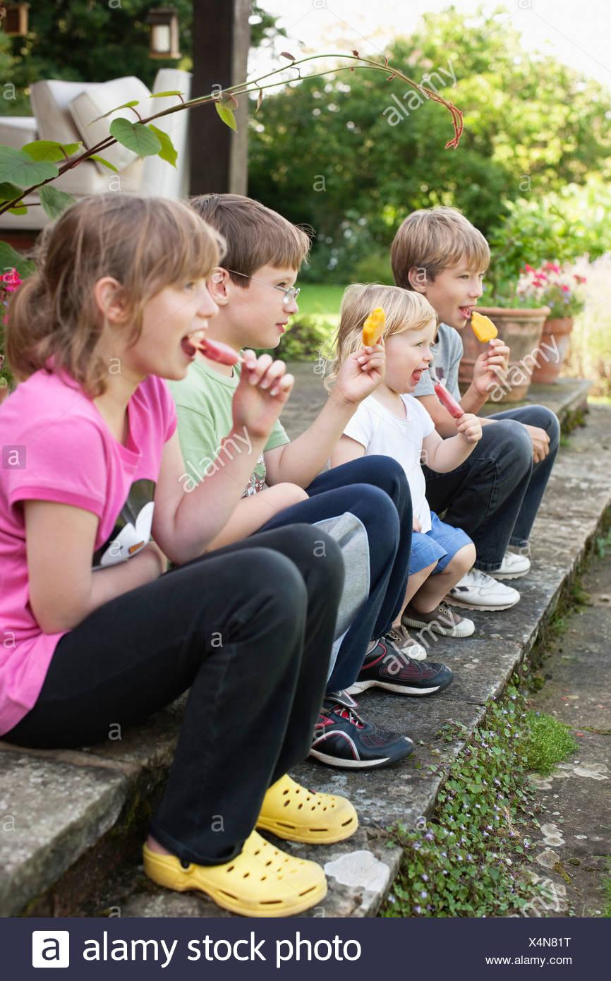 Children enjoying popsicle outdoors - Stock Image