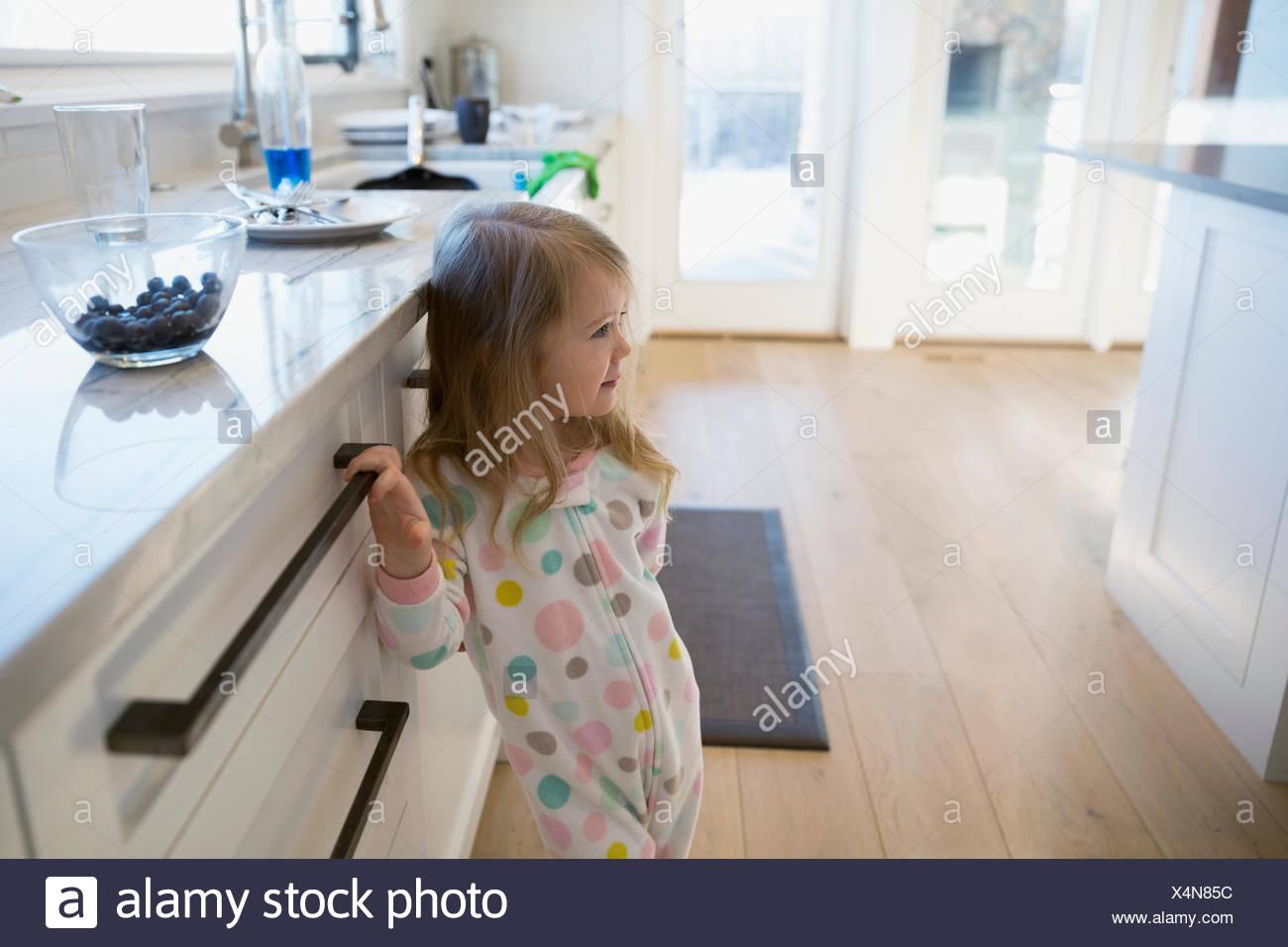 Cute girl in polka-dot pajamas in kitchen - Stock Image