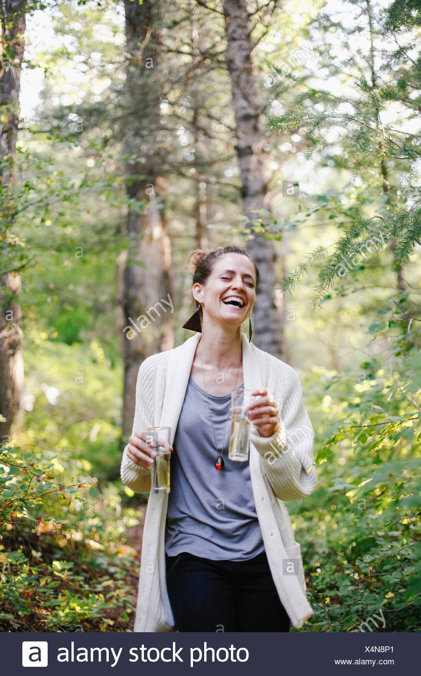 A woman standing in a glade in woodland holding two tall glasses of champagne. - Stock Image