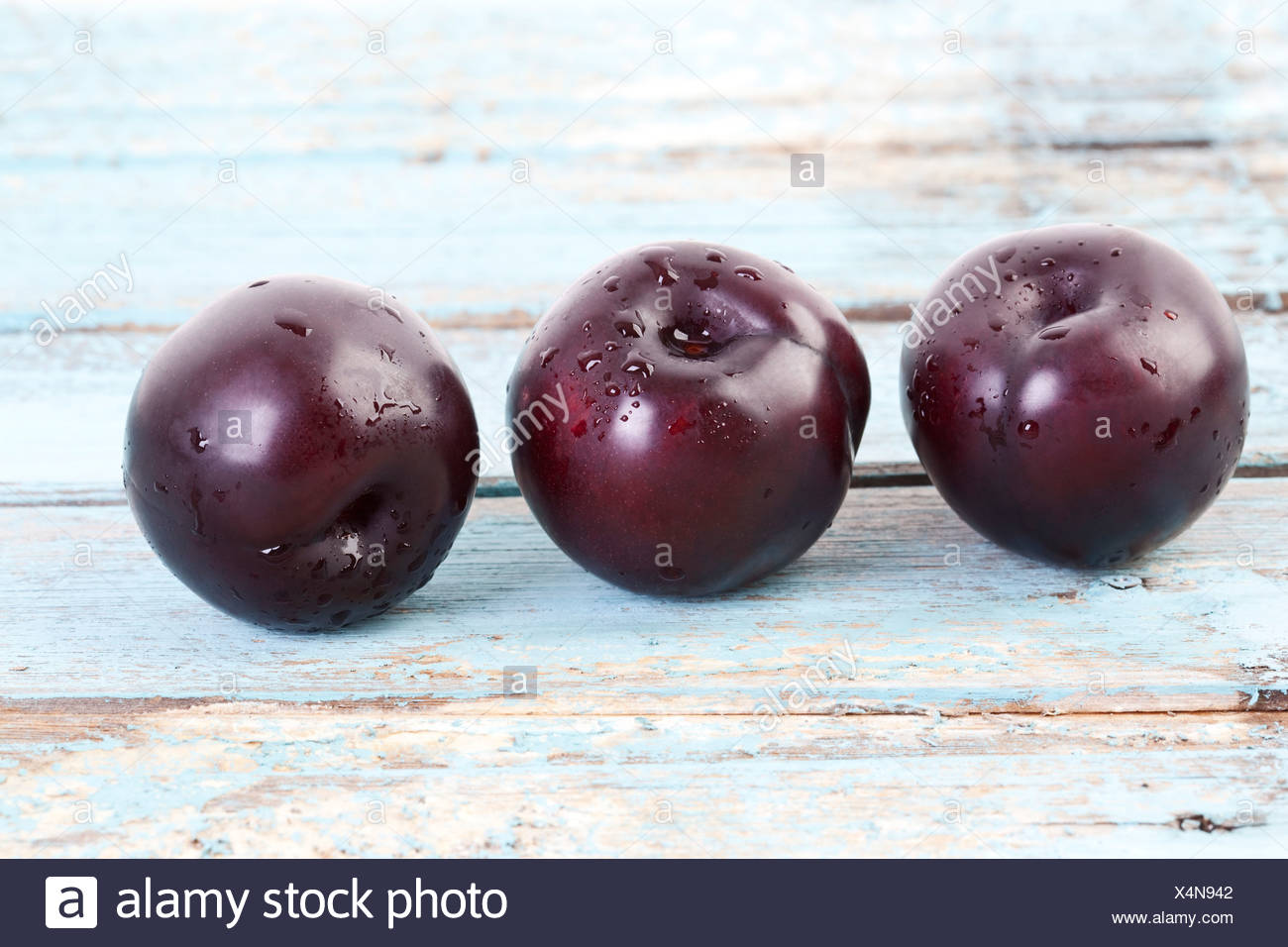 Three plums on wooden table, close up - Stock Image