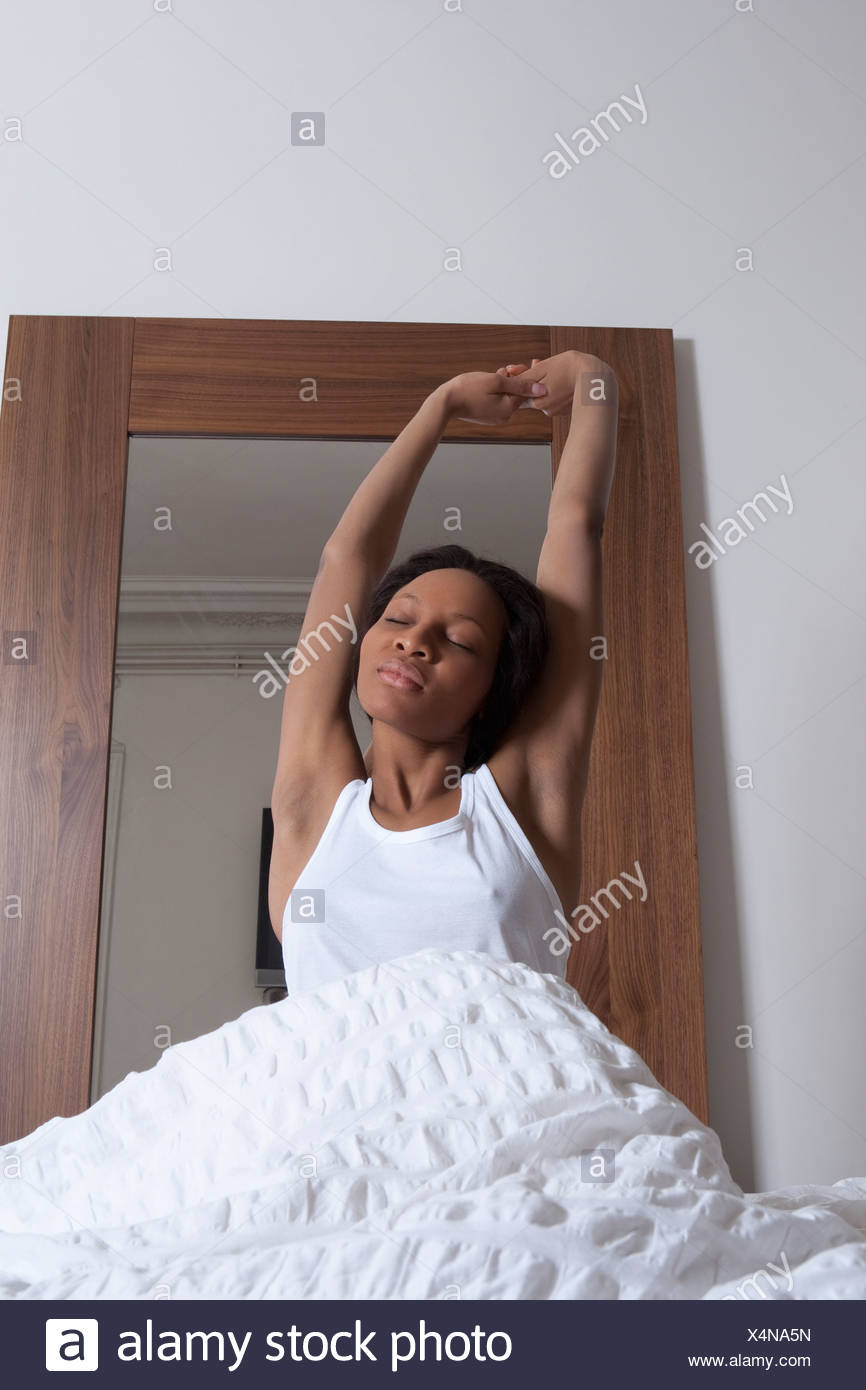 Woman stretching in bed - Stock Image