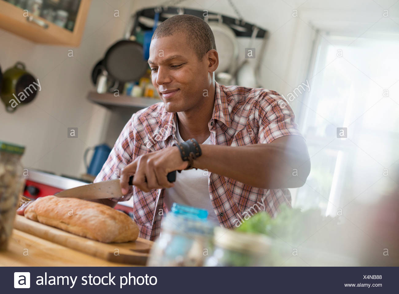 A man in a kitchen slicing a loaf of bread. - Stock Image