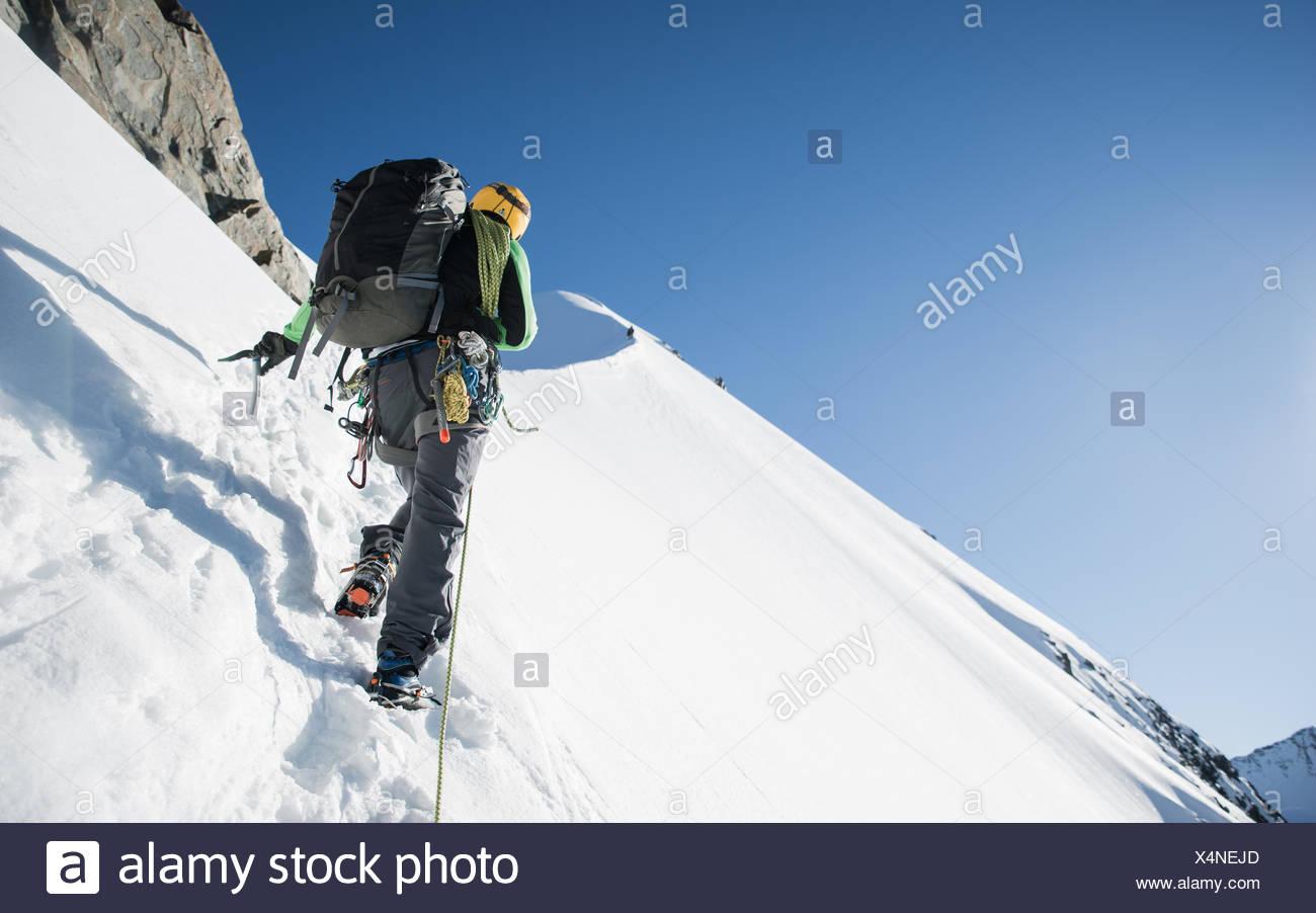 Man mountain climbing at Bianco Ridge, Swiss Alps, Bernina region, Switzerland - Stock Image