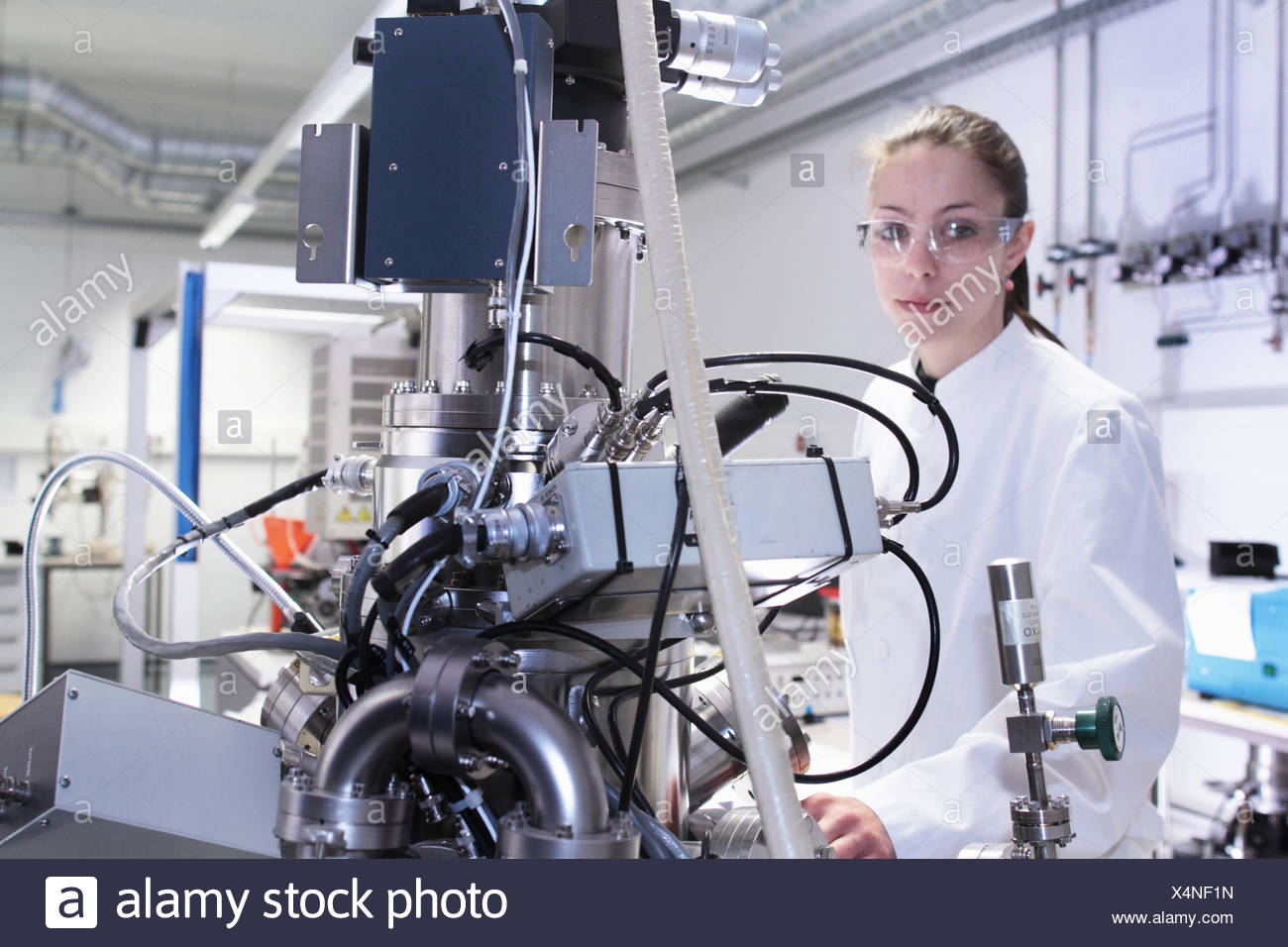 Portrait of female lab technician with scientific equipment - Stock Image