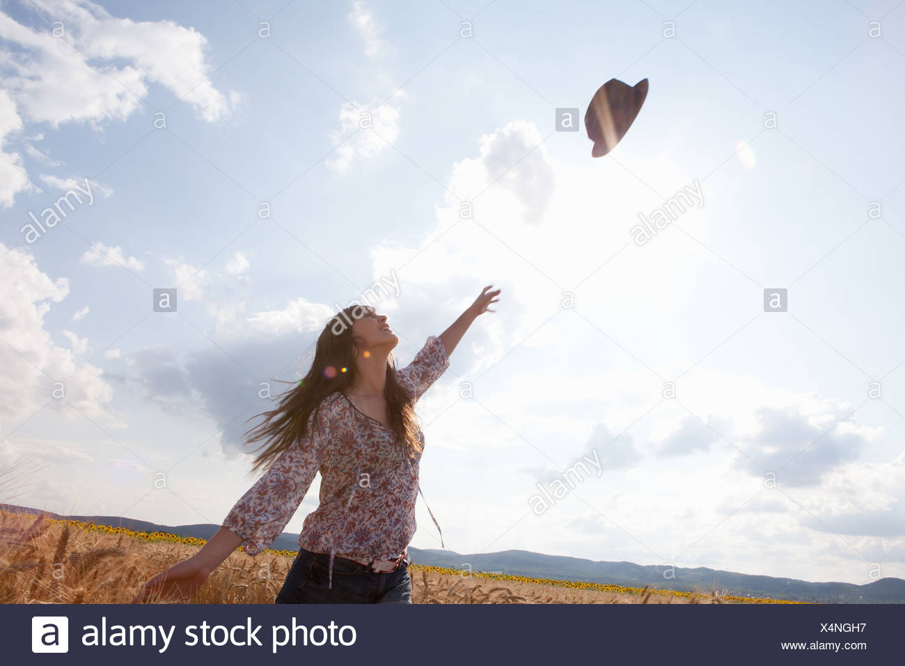 Mid adult woman throwing hat in air - Stock Image