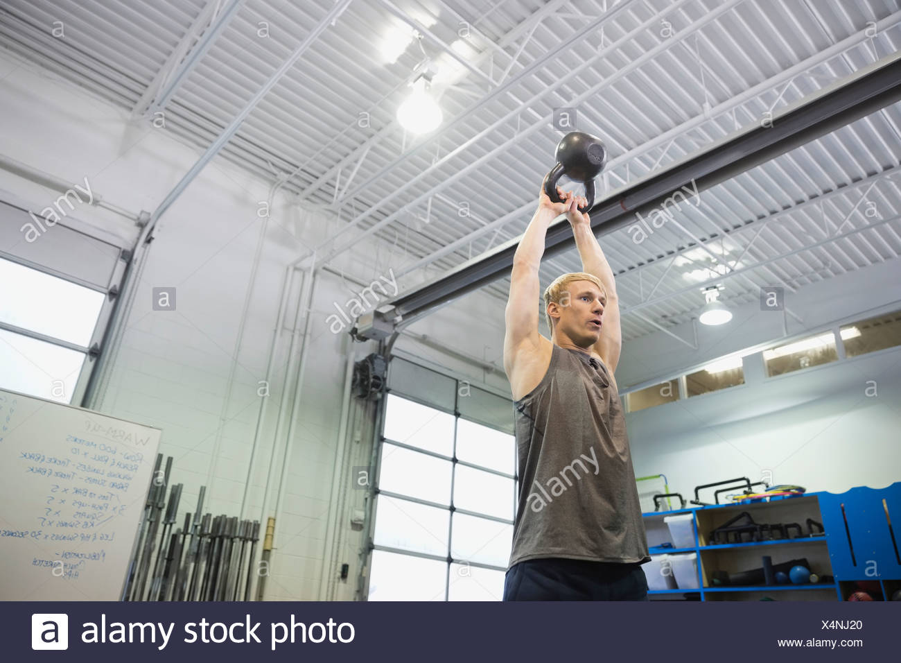 Man performing overhead kettlebell throws - Stock Image