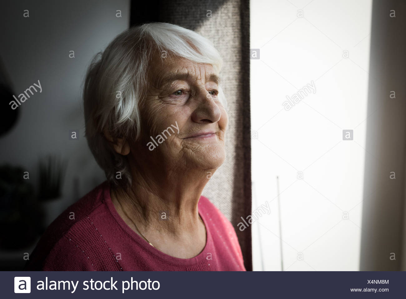 Senior woman standing near window - Stock Image