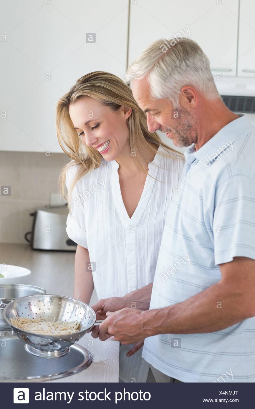 Couple draining spaghetti in colander - Stock Image