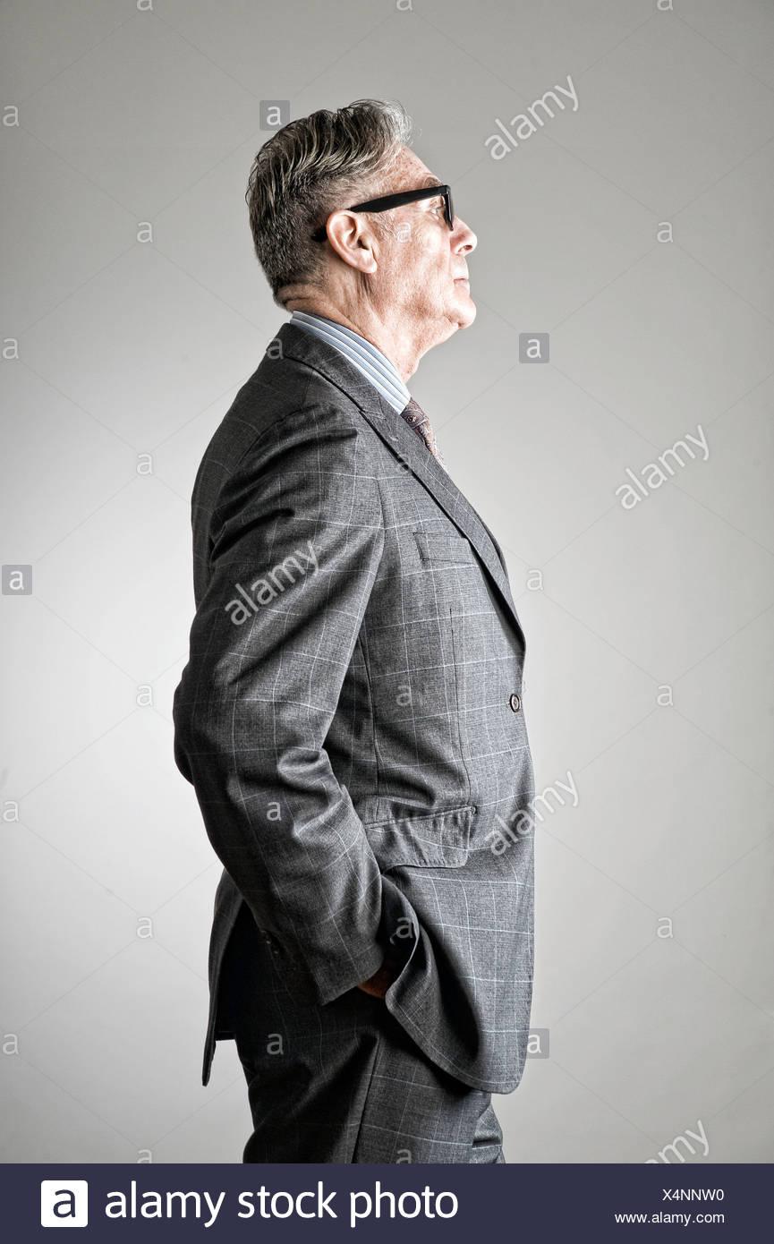 Portrait of senior man, wearing suit, side view - Stock Image