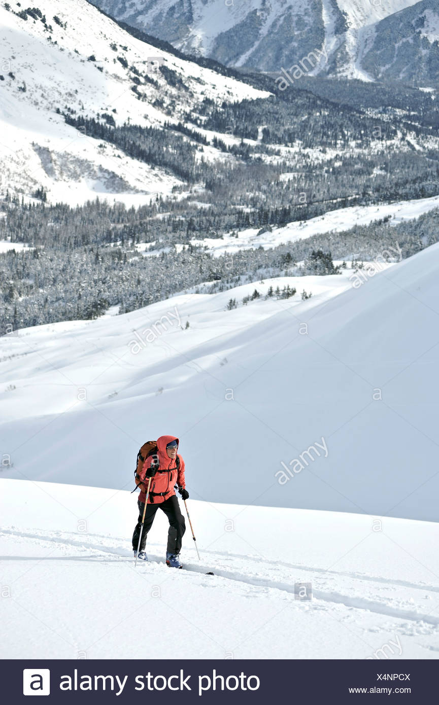 Woman skier backcountry skiing in PMS Bowl in Turnagain Pass, Chugach National Forest, Southcentral Alaska, Winter Stock Photo