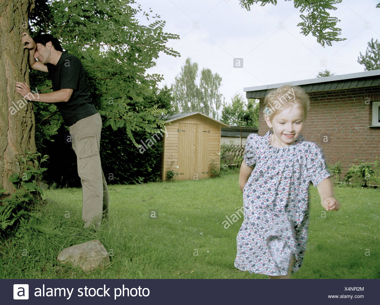 Garden, father, subsidiary, hide-and-seek, man, parent, 30-40 years, parent, single parent, single, tree, lean, eyes head straight, count, wait, look away, child, girl, 4 - 5 years, infant, childhood, happy, fun, game, game fun, play, run away, run, hide, - Stock Image