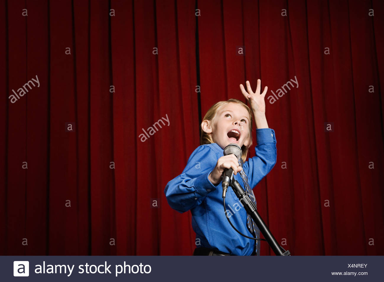 Boy singing on stage - Stock Image