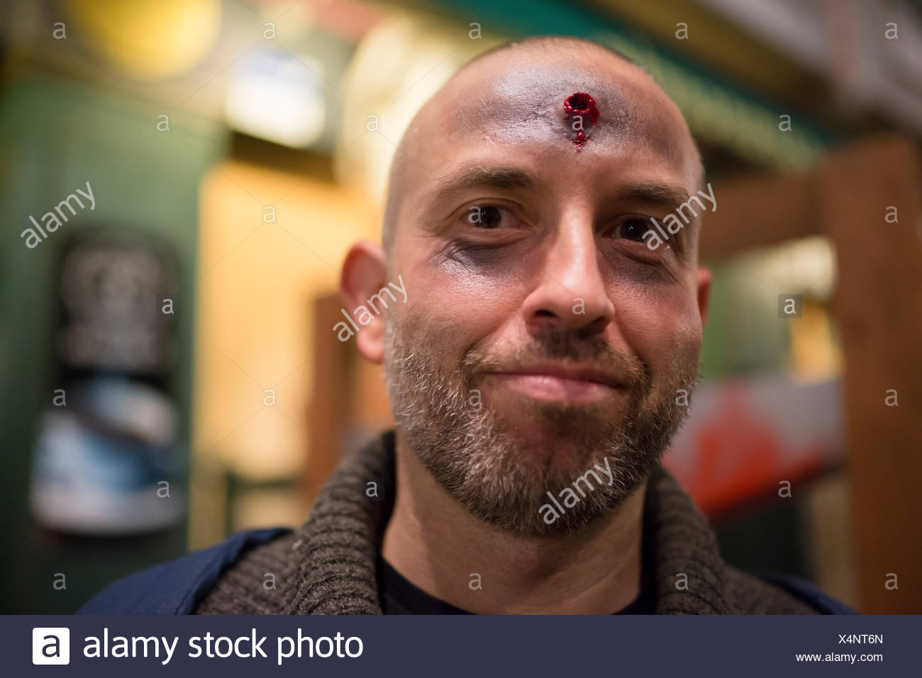Bearded man with fake shot in his forehead at Halloween - Stock Image