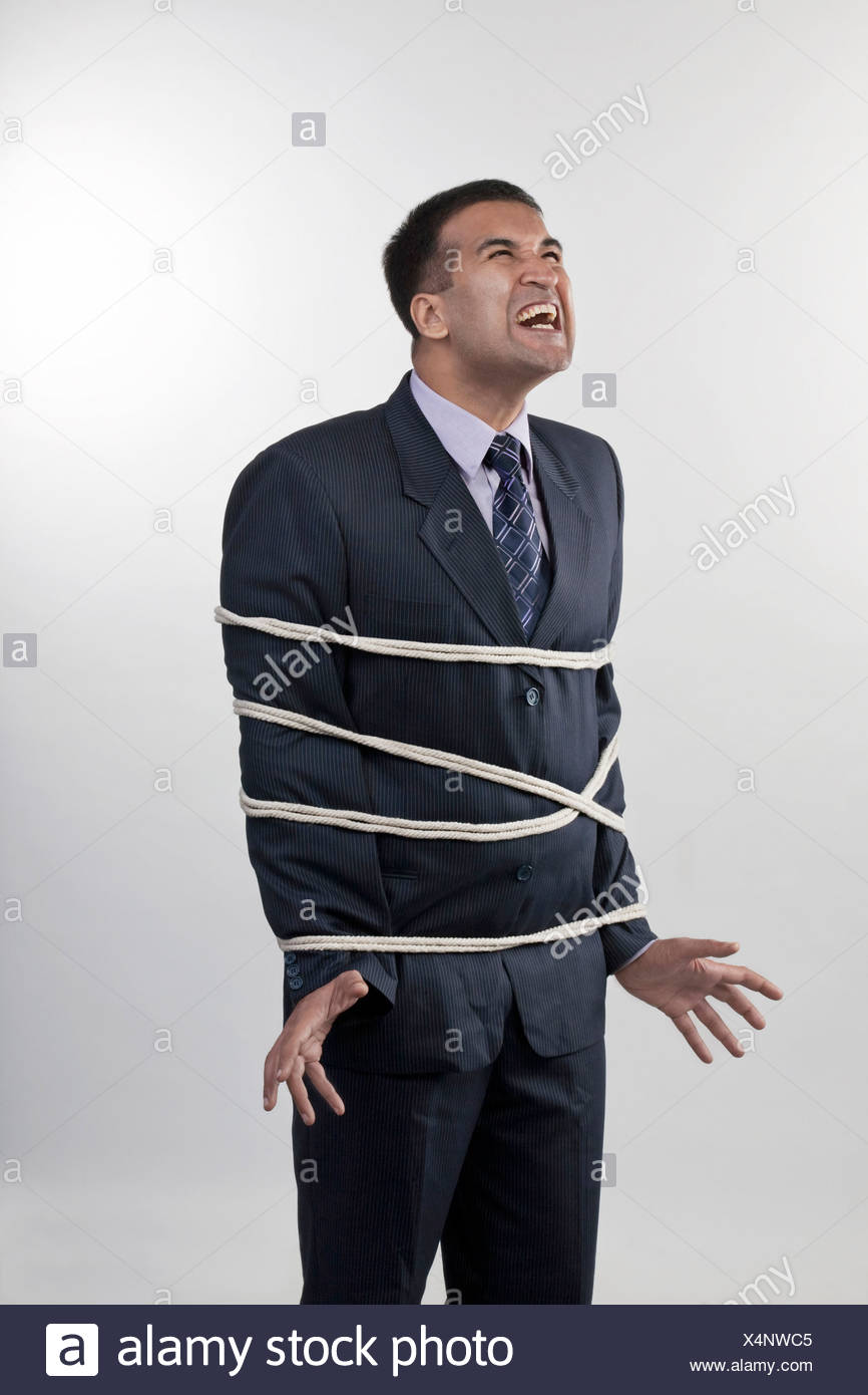 Businessman tied up with rope - Stock Image