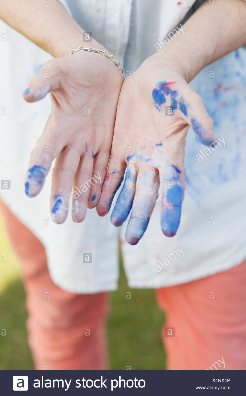 Midsection of senior female painter showing messy hands outdoors - Stock Image