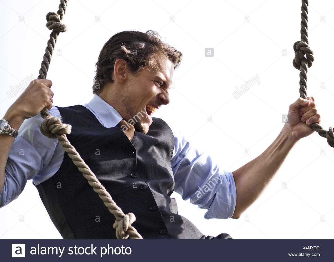 Strong, able businessman climbing ropes - Stock Image