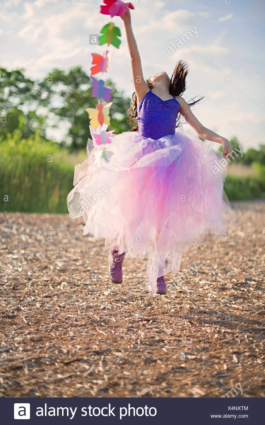 Girl in a pink tutu jumping in the air - Stock Image
