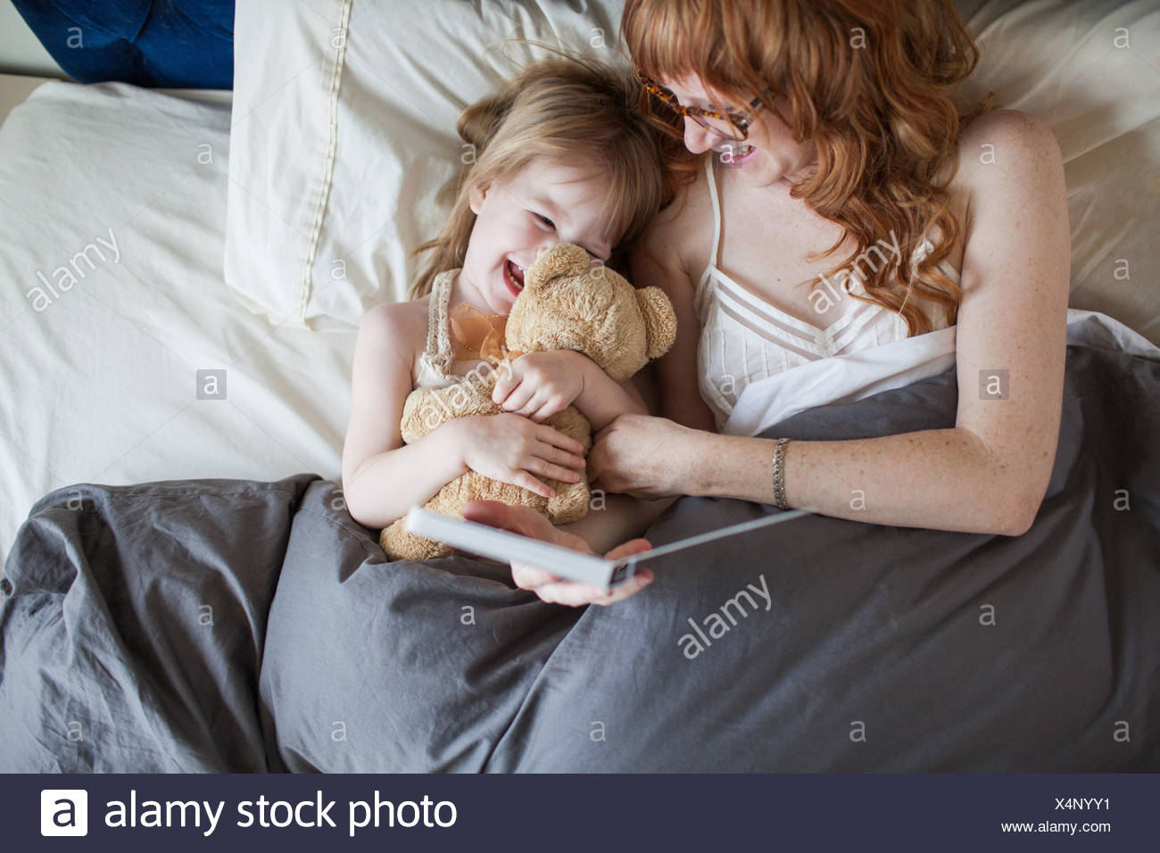 Mother and daughter lying on bed cuddling soft toy - Stock Image