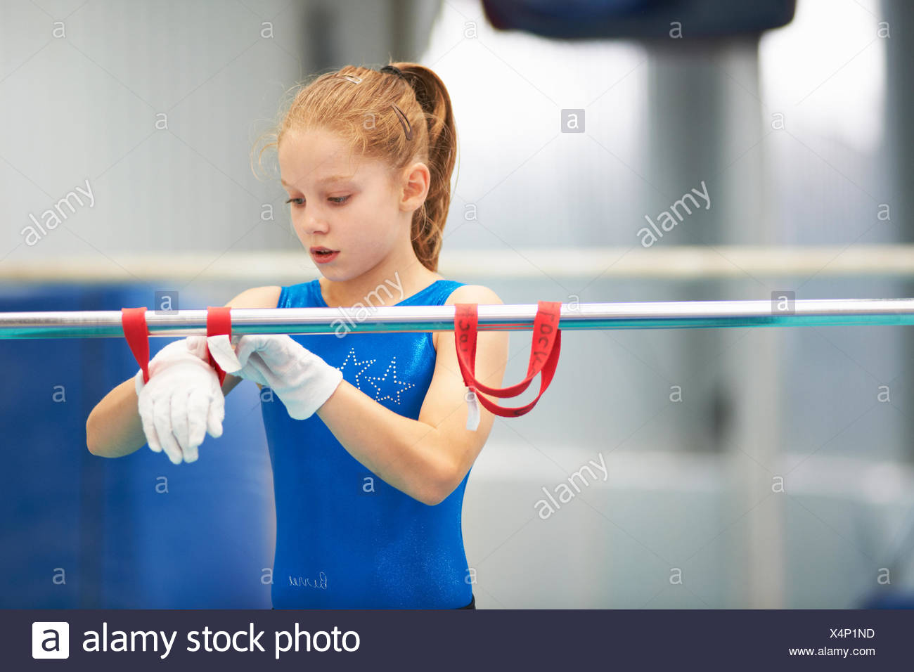 Young gymnast using training wrist straps to aid practise on bars - Stock Image