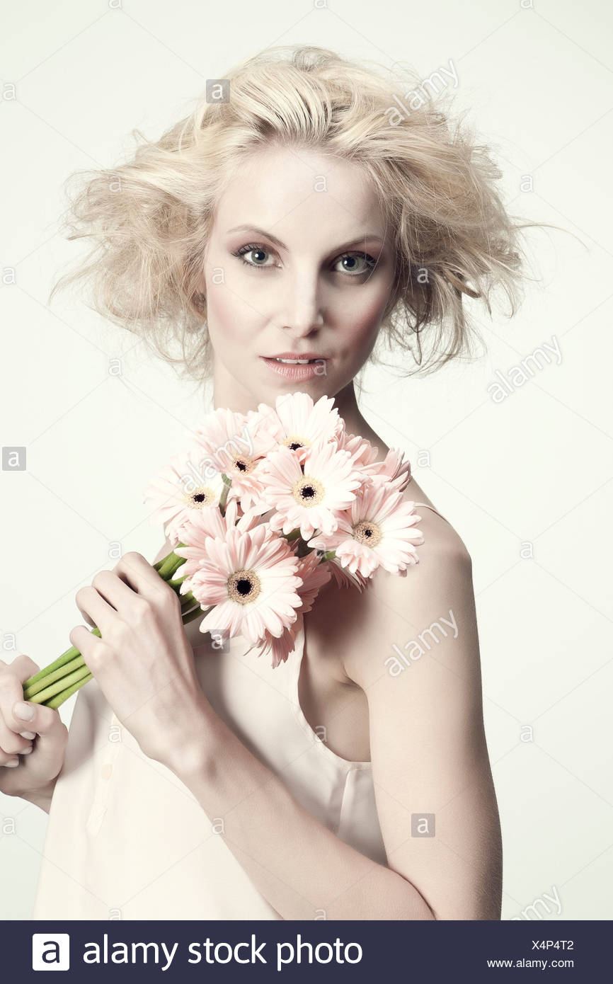 Young woman holding bunch of gerbera daisies, portrait - Stock Image