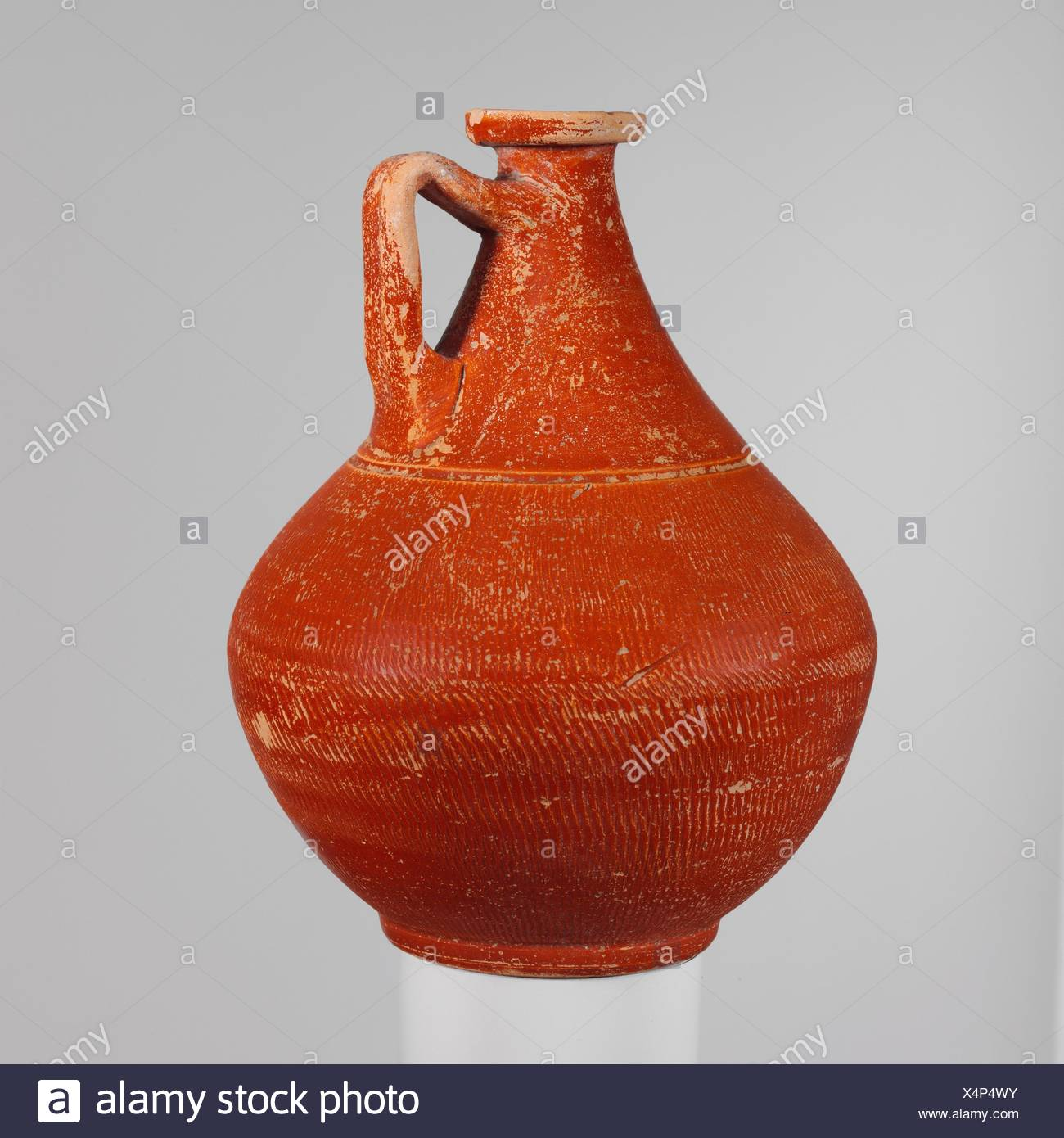 Terracotta jug. Period: Early Imperial; Date: 2nd half of the 1st century A.D; Culture: Roman; Medium: Terracotta; red-glaze; Dimensions: 6 1/4in. - Stock Image