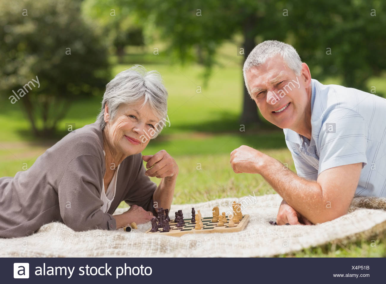Happy senior couple playing chess at park - Stock Image
