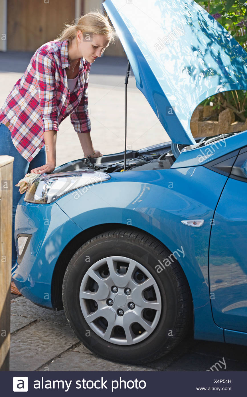 Woman With Broken Down Car Looking Under Bonnet - Stock Image