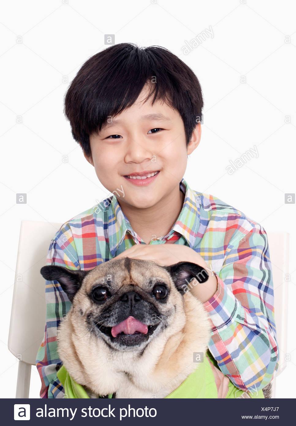 Portrait of Boy holding pet pug - Stock Image