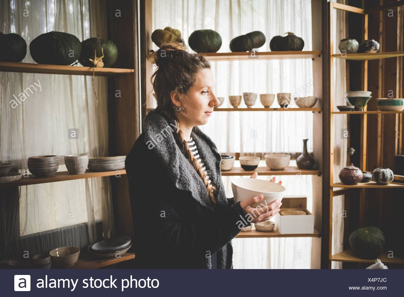 Side view of young woman holding ceramic dish in front of shelves displaying clay pots and pumpkins - Stock Image