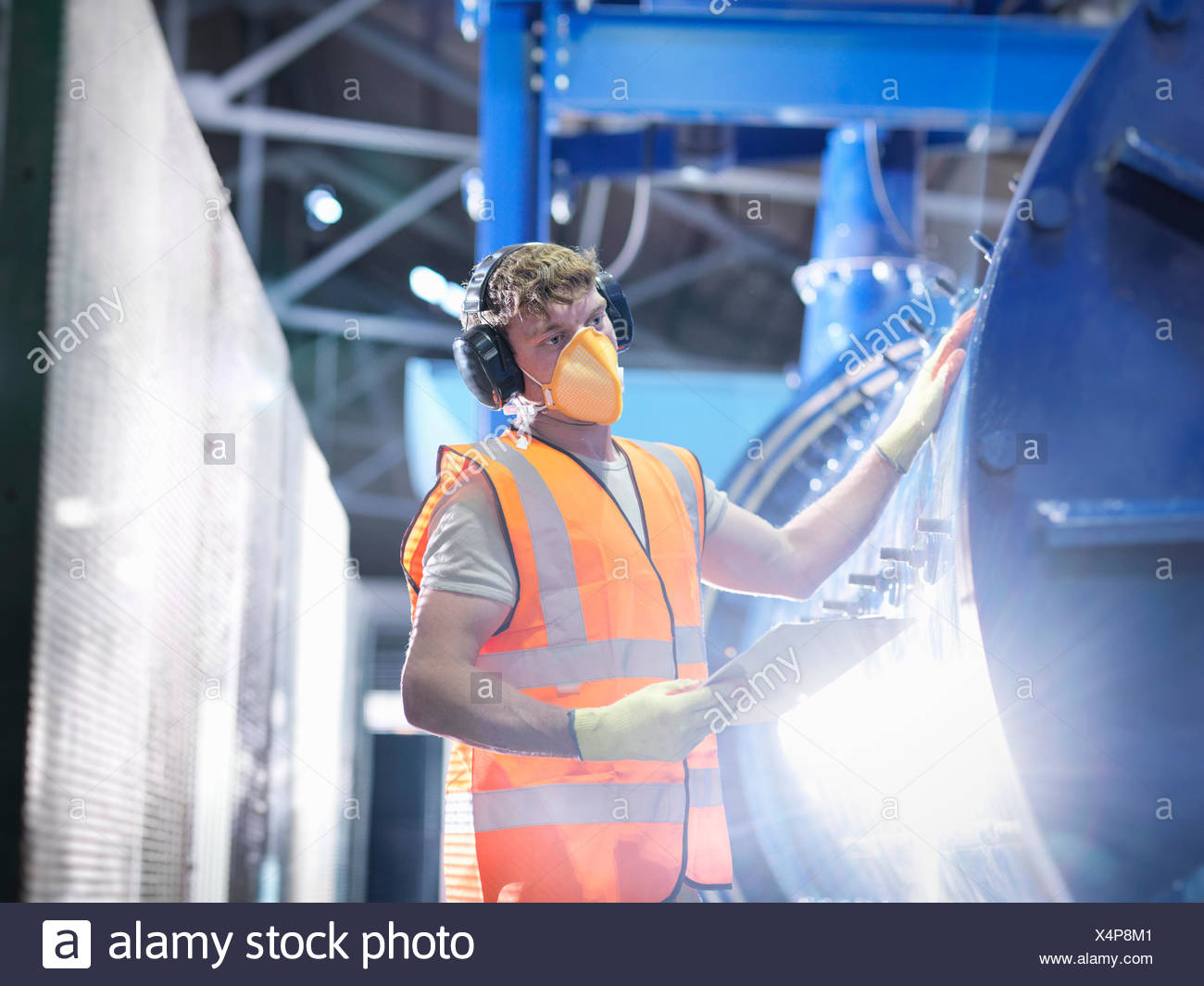 Worker checking metal ore grinding mill - Stock Image
