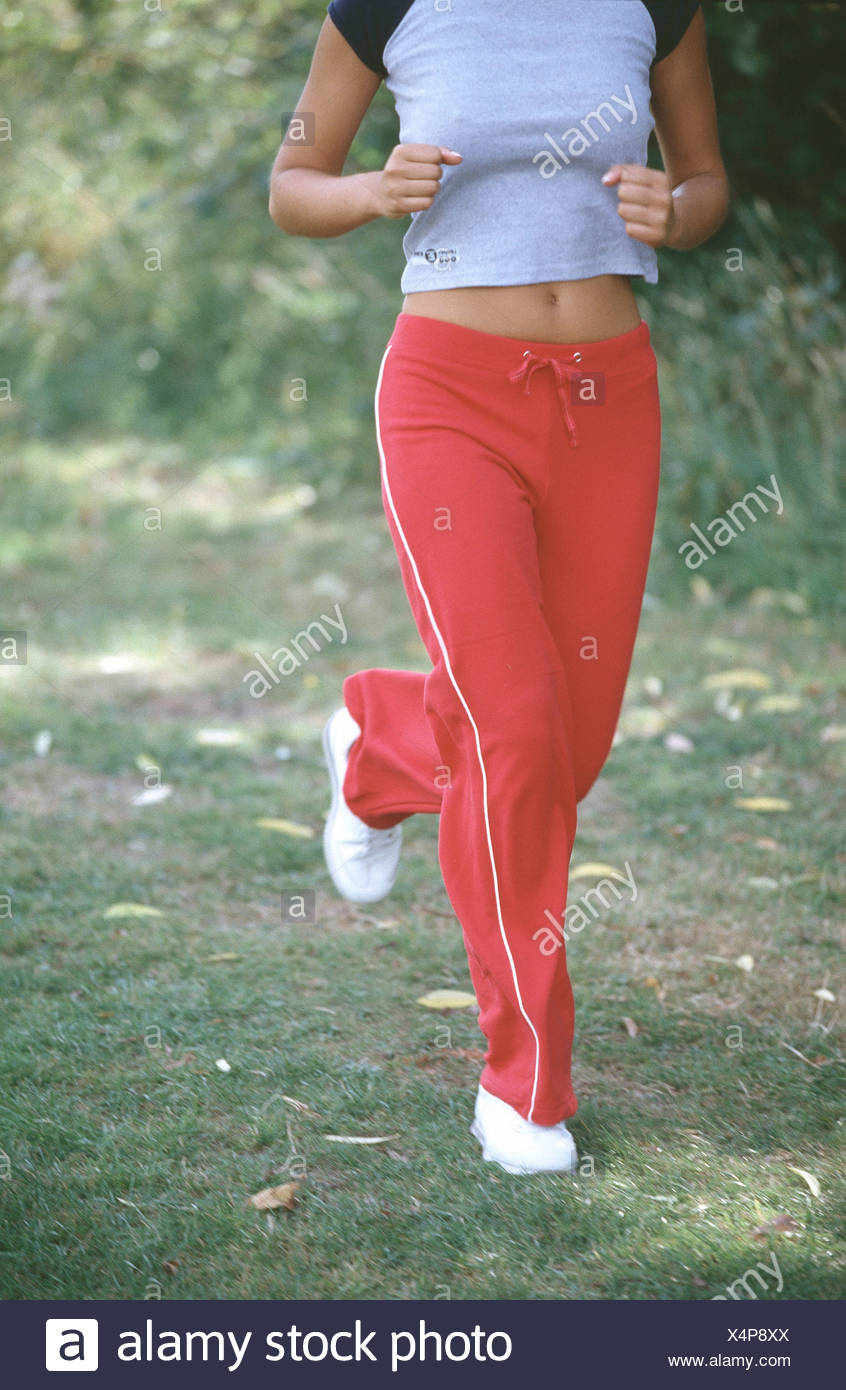 c3e59a2de4c9 Cropped female wearing cropped grey t shirt with navy blue sleeves red tracksuit  bottoms and white trainers jogging in park