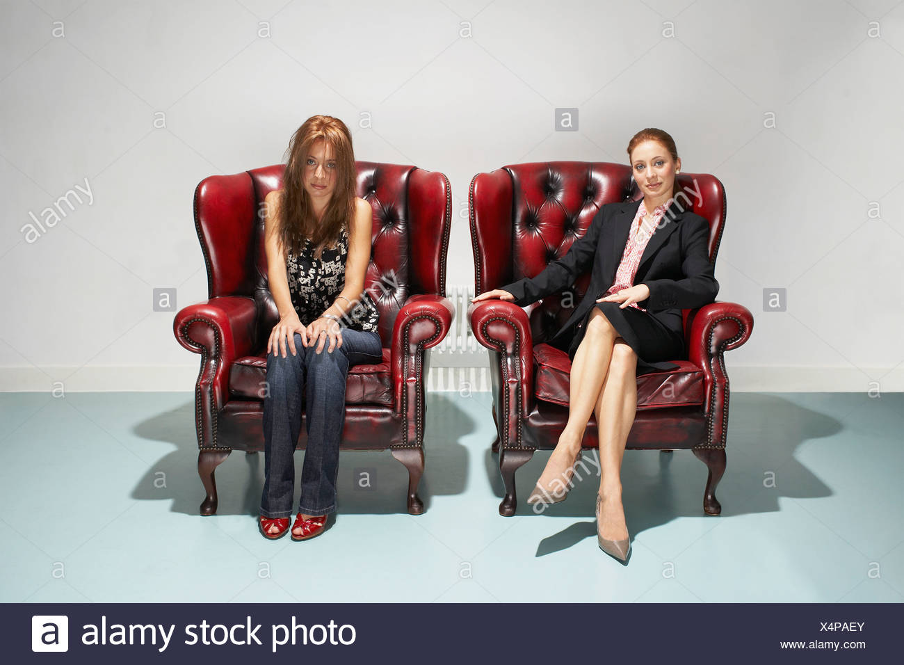 Businesswoman and disheveled woman in comfy leather chairs - Stock Image