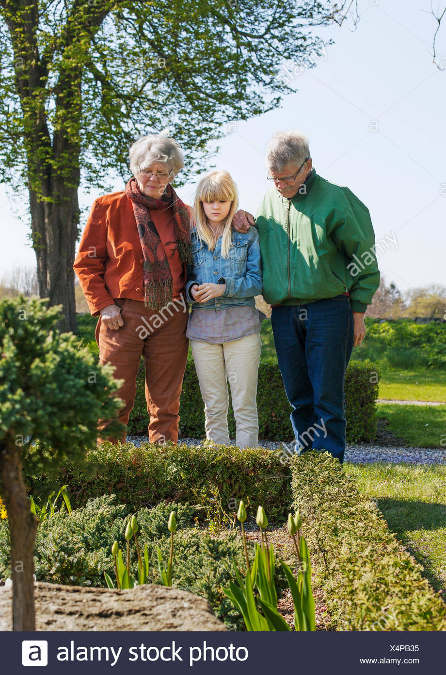 Girl and her grandparents in churchyard garden Stock Photo